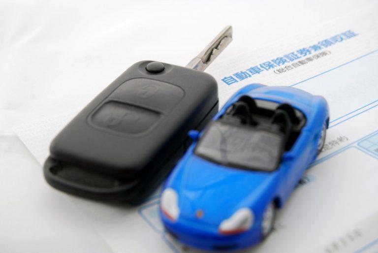 保険証券の上に載っているオモチャの車とその鍵