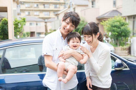 車の前で子供抱っこする夫婦
