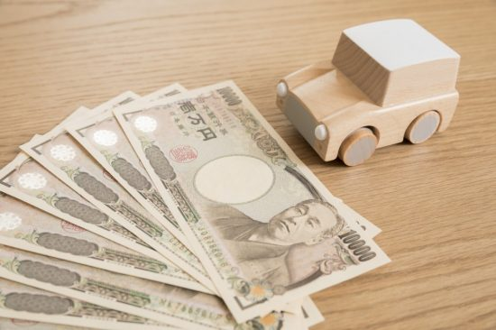 車の置物と1万円札