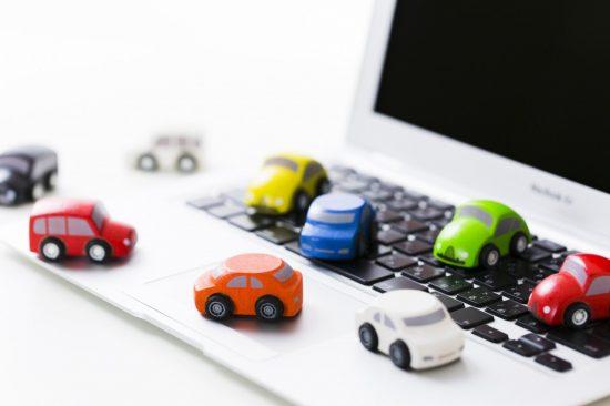 パソコンの上に並んでいる車の模型