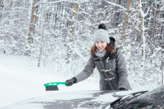 車の雪下ろしをする女性