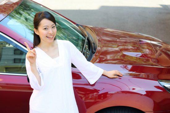 笑顔で車の前に立つ女性