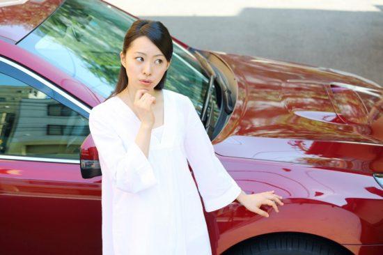 車の前で考える女性