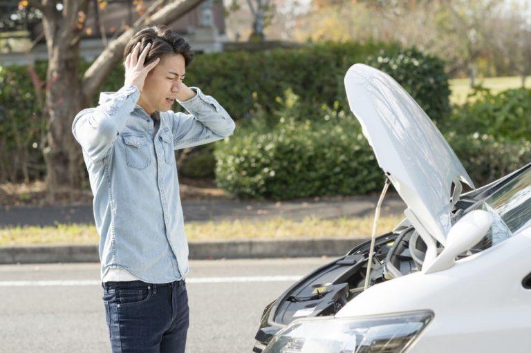 車のトラブルで困っている男性