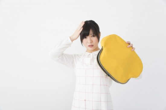 空っぽの財布を持った女性