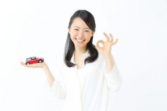 車を手に乗せてOKサインを出す女性