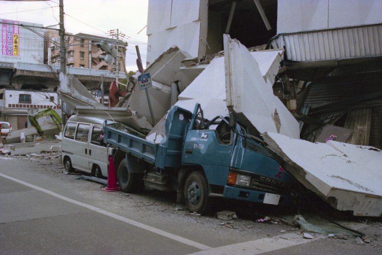 地震で倒壊したビルの下敷きになっている車