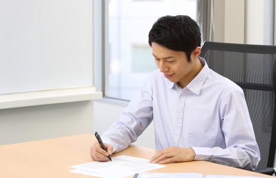 変更手続書類を書く男性