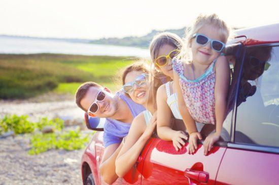 車の窓から顔を出す4人家族