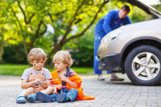 整備中の車の前で工具で遊ぶ子供