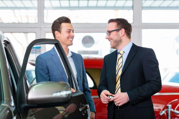 車の営業マンと交渉する男性