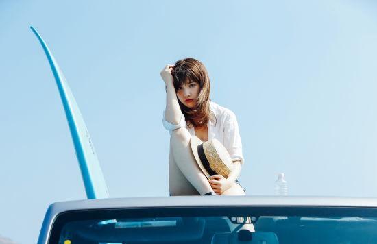 車のルーフトップに座る女性