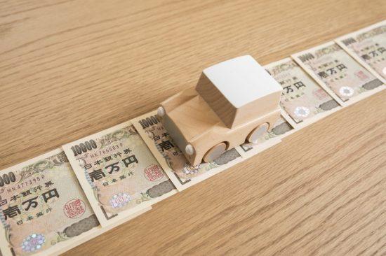お金の上を走る車のおもちゃ