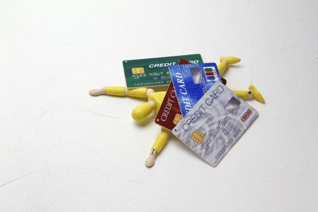 クレジットカードに押しつぶされる人形