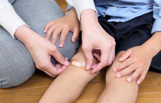 怪我した子供の足に絆創膏を貼る