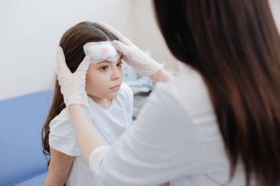 頭のケガの治療をうける子供