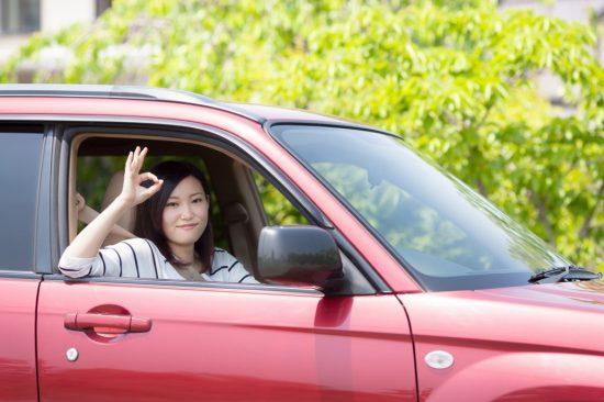 運転席からO運転席からOKサインを出す女性Kサインを出す女性