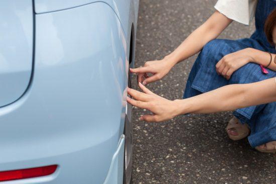 車の傷を確かめる女性