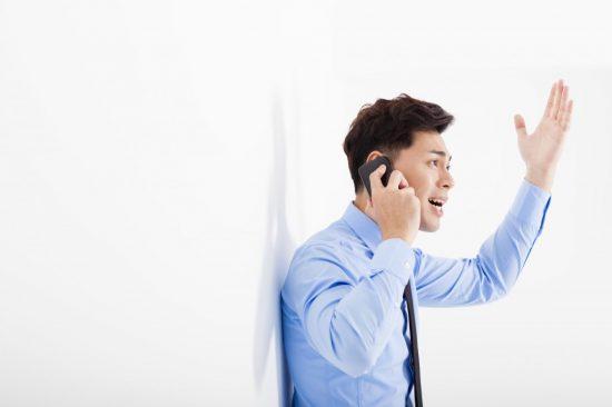 電話でクレームを言う男性