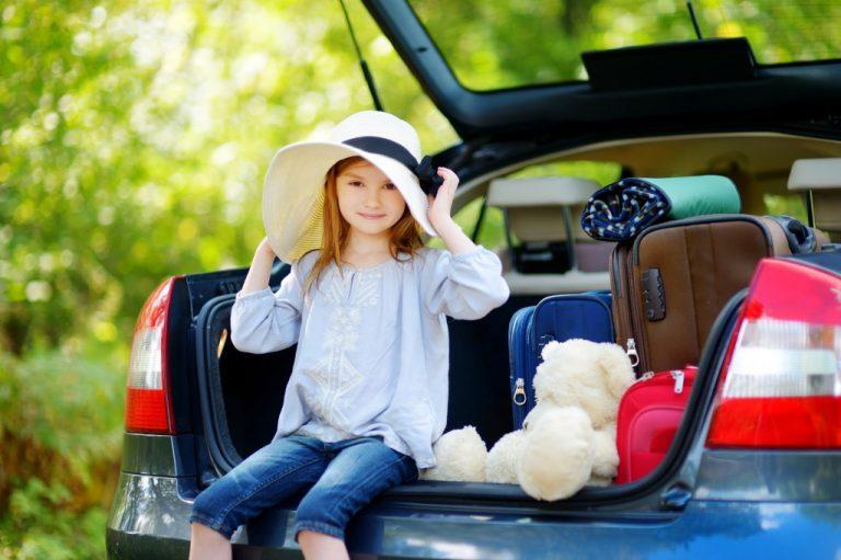 車のトランクに座る少女と積載された物