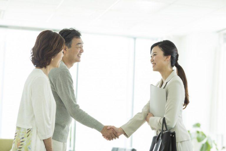 自動車保険のセールスレディーと握手をする夫婦