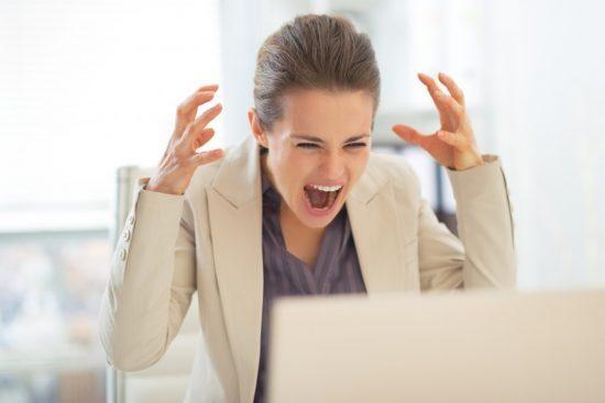 パソコンの前で叫ぶ女性