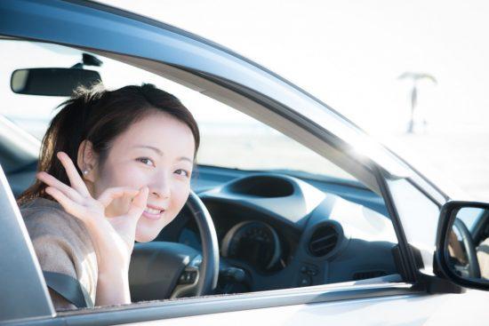 車に乗ってOKサインを出す女性