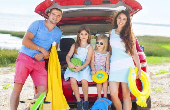 車の周りで記念写真を撮る家族