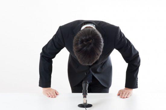 報道発表で謝罪する男性