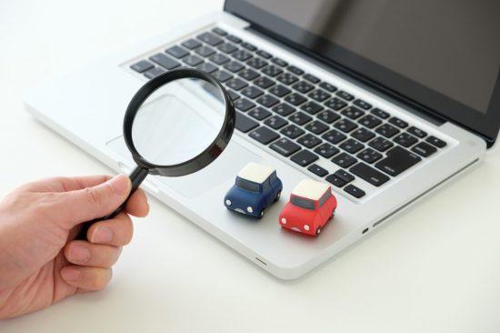 虫眼鏡で2台のおもちゃの車を観察
