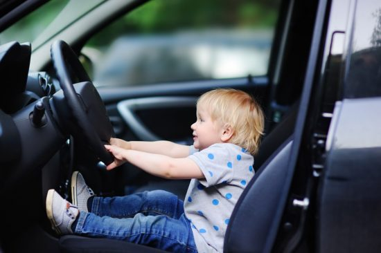 車の運転席に座る子供