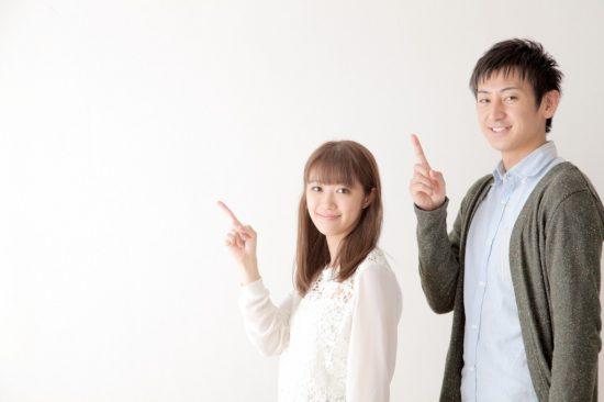 指を立てる男女